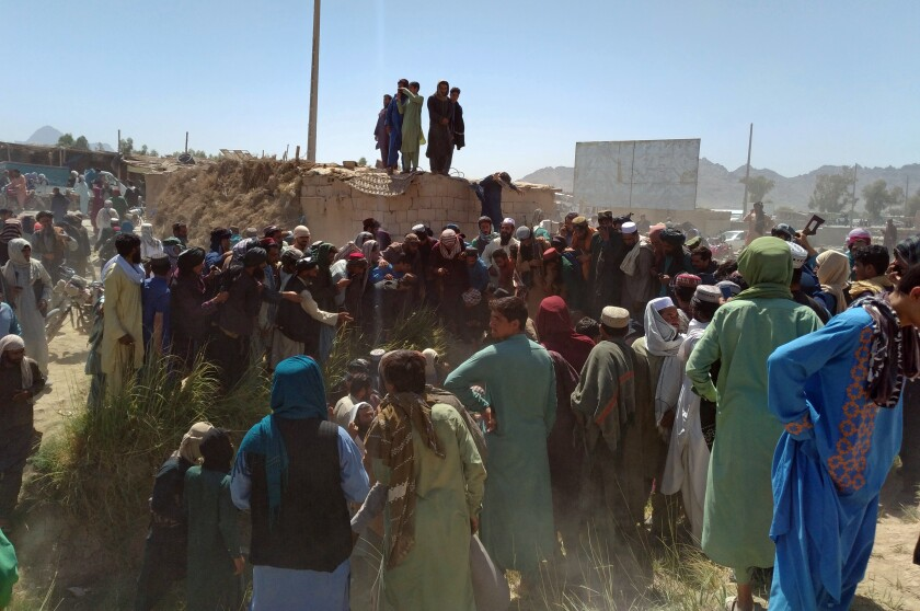 Taliban fighters and Afghans gather