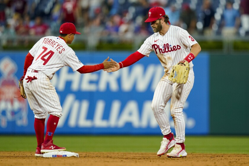 Philadelphia Phillies' Bryce Harper, right, celebrates a win with Ronald Torreyes, left, following the ninth inning of a baseball game against the Atlanta Braves, Friday, July 23, 2021, in Philadelphia. (AP Photo/Chris Szagola)