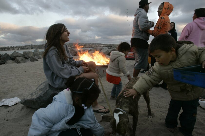 Cierra Iriarte, 15, laughs with members of her family as Camillle Randall, 4, (front left) and Romeo Iriarte, 4, play with a dog at South Mission Beach by a fire pit on Mother's Day.
