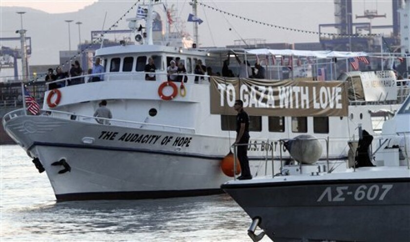 """Activists boat """"Audacity of Hope"""" is escorted by the Greek coast guard ship in town of Peramat, near Athens, Greece, Friday, July 1, 2011. Greece on Friday banned ships heading to the Gaza Strip from leaving Greek ports, and a vessel carrying several dozen American protesters which left port without permission was ordered to return. (AP Photo/Darko Bandic)"""