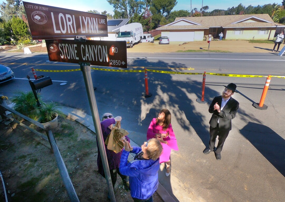 Rabbi Mendel Goldstein of Chabad of Poway, right, looks on, as Jane Cohen, left, Lidia Kotlyar, foreground, and Roneet Lev, unveil the street sign, Lori Lynn Lane at the intersection of Stone Canyon Road, December 20, 2019 in Poway, California.