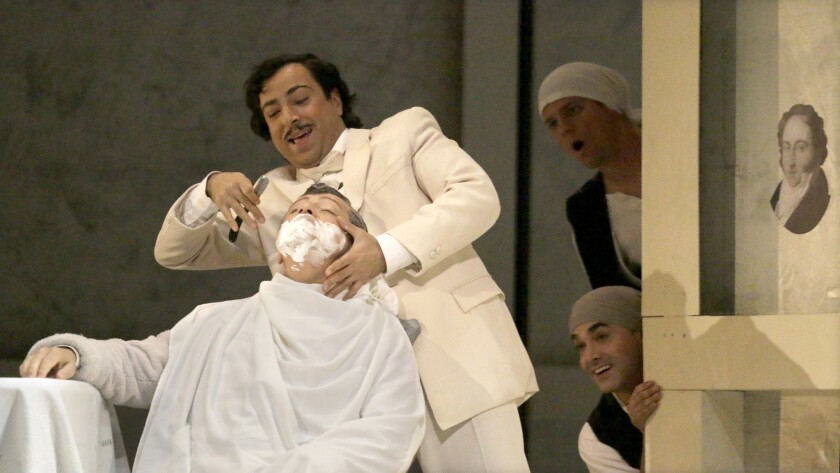 """Alessandro Corbelli as Doctor Bartolo (being shaved) and Rodion Pogossov as Figaro in Los Angeles Opera's """"The Barber of Seville"""" at Dorothy Chandler Pavilion in Los Angeles."""
