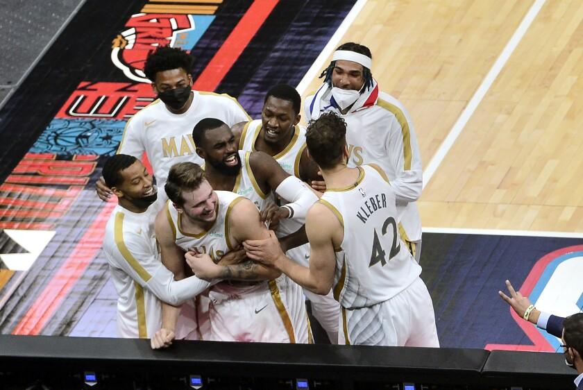 Luka Doncic (centro, abajo), de los Mavericks de Dallas, es felicitado por sus compañeros tras lograr el enceste del triunfo sobre los Grizzlies de Memphis, el miércoles 14 de abril de 2021 (AP Foto/Brandon Dill)