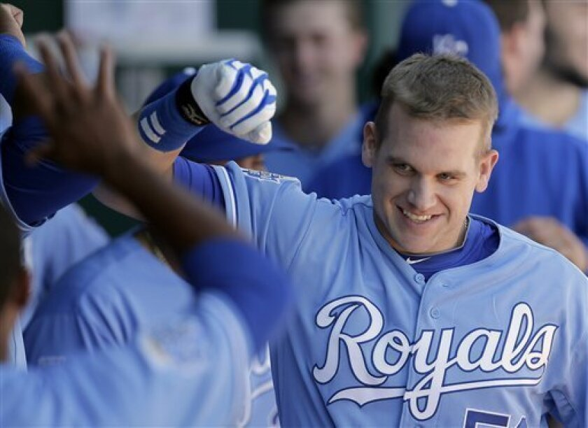 Kansas City Royals' Adam Moore celebrates in the dugout after hitting a solo home run during the third inning of a baseball game against the Cleveland Indians, Sunday, Sept. 23, 2012, in Kansas City, Mo.