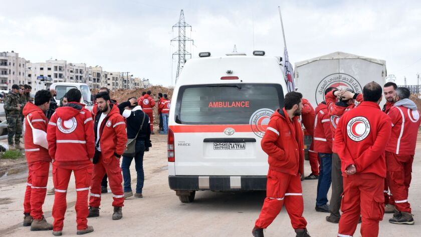 Syrian Red Crescent paramedics wait on a highway in eastern Aleppo for buses evacuating civilians from the government-held villages of Fuaa and Kafraya on April 14.