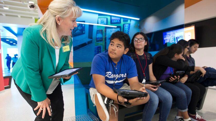 La voluntaria del programa Junior Achievement, Debbi Ortiz, habla con alumnos de décimo curso sobre cómo preparar un presupuesto.