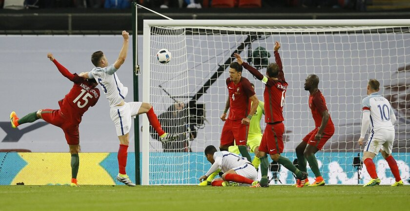 England's Gary Cahill, second left, fails to score during the international friendly soccer match between England and Portugal at Wembley stadium in London, Thursday, June 2, 2016. (AP Photo/Kirsty Wigglesworth)