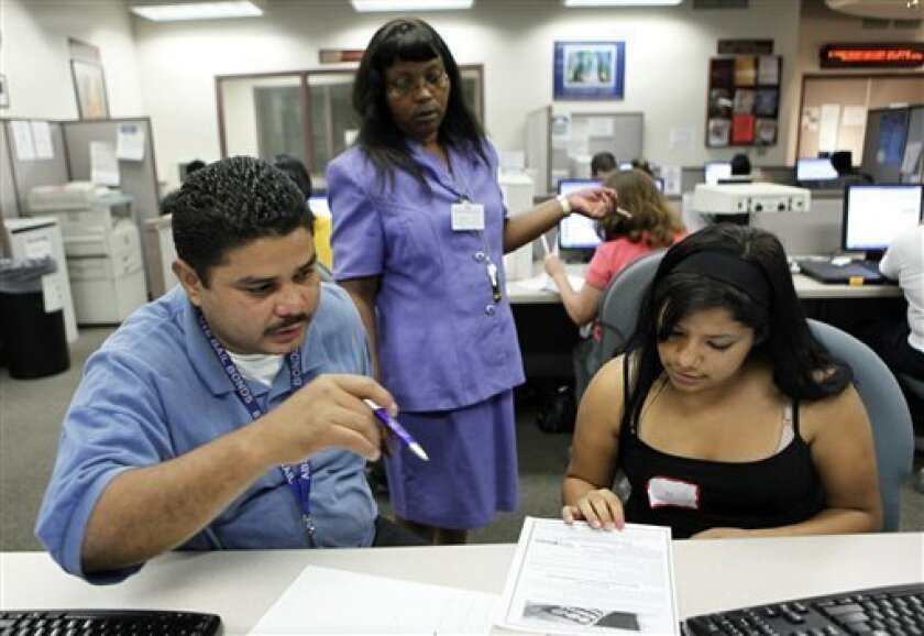 In this Oct. 6, 2009 photo, people look for job opportunities at the Metro North Work Source Center in Los Angeles. Job losses are expected to continue at least into the middle of next year, likely driving the unemployment rate above 10 percent from 9.8 percent last month. It could take three or fo