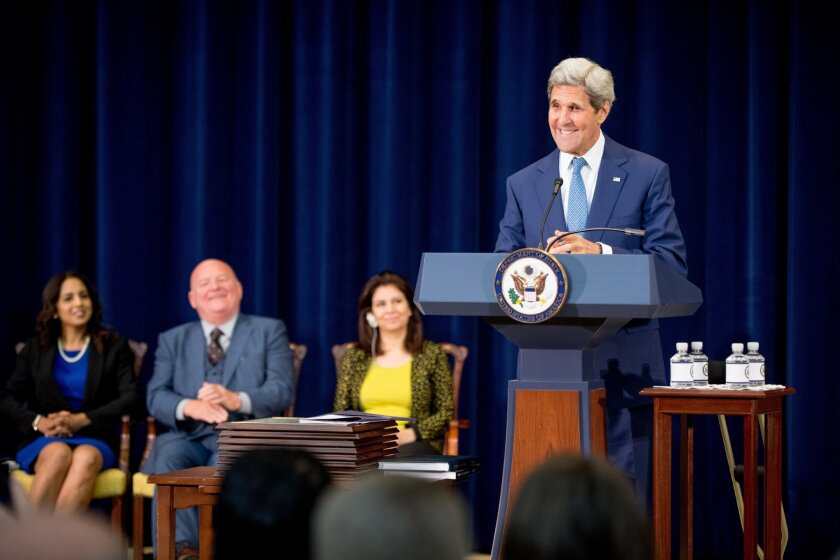 """Secretary of State John Kerry, accompanied by """"2015 Trafficking in Persons Report heroes,"""" whose efforts have made an impact on the global fight against modern slavery, speaks during a news conference at the State Department on July 27."""