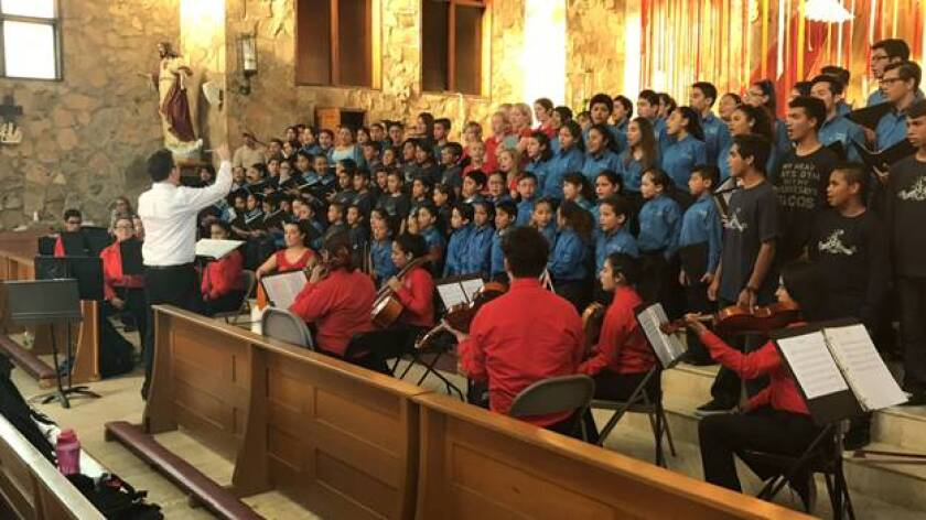 """The One World Children's Foundation seeks support to connect San Diego-area youths and children across the border through arts and music as part of the """"Building Bridges Beyond Borders"""" program led by the nonprofit's founder and artistic director, Dr. Aaron Mitchell. The choir will present music from """"The Greatest Showman,"""" in Spanish and English, in a benefit concert st 7:30 p.m. Thursdaywith Mariachi Diamante at Calvary Lutheran Church in Solana Beach. Free admission; donations are appreciated. The nonprofit is also accepting applications for music ambassadors for """"The Million Dreams Project,"""" a humanitarian project in Mexico, providing music classes to orphanages and children's groups and bringing children together for cultural exchange and concert programs in Spanish and English. Donations will support the June 21 project in Ensenada and ongoing projects in Tecate, Tijuana and Manaus, Brazil. Pictured is Mitchell leading the final rehearsal in a previous One World project in Ensenada. Visit oneworldchildrensfoundation.org and gofundme.com/oneworldborder."""