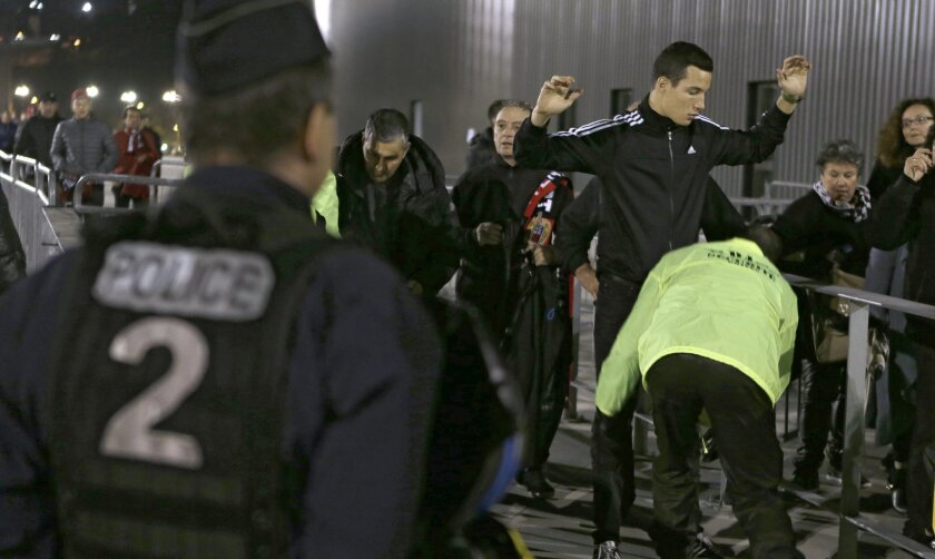 Supporters are checked by security at the entrance of the Nice stadium before the French League One soccer match between Nice and Lyon, Friday, Nov. 20, 2015, in Nice, southeastern France. Security at the stadium is enhanced after last Paris Friday's attacks that killed 129 people and wounded hundreds of others. (AP Photo/Lionel Cironneau)