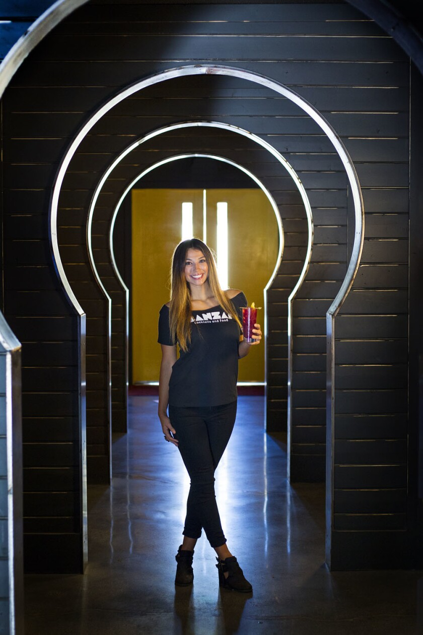 Bartender Chelcie Lopez holds a Smoke Show drink at the newly-opened Banzai Bar in the Midway District. (K.C. Alfred)