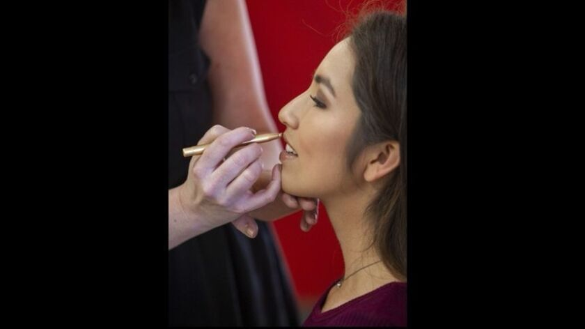 "Julie Schweers, left, applies makeup to Gina Gonzalez, 17, during the ""Pick Your Prom Dress Event"" a"