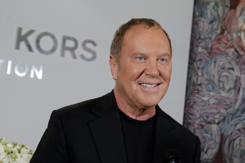 FILE - Designer Michael Kors appears before his Spring 2017 collection is modeled during Fashion Week, in New York, on Sept. 14, 2016. Kors loves fashion, but he also loves the Broadway theater. He celebrated that love as he marked his 40th anniversary as a designer this week, with a show that showcased the razzle-dazzle of Broadway. His models sashayed down a runway that was actually West 45th street, in the heart of Manhattan's still-shuttered theater district. (AP Photo/Richard Drew, File)