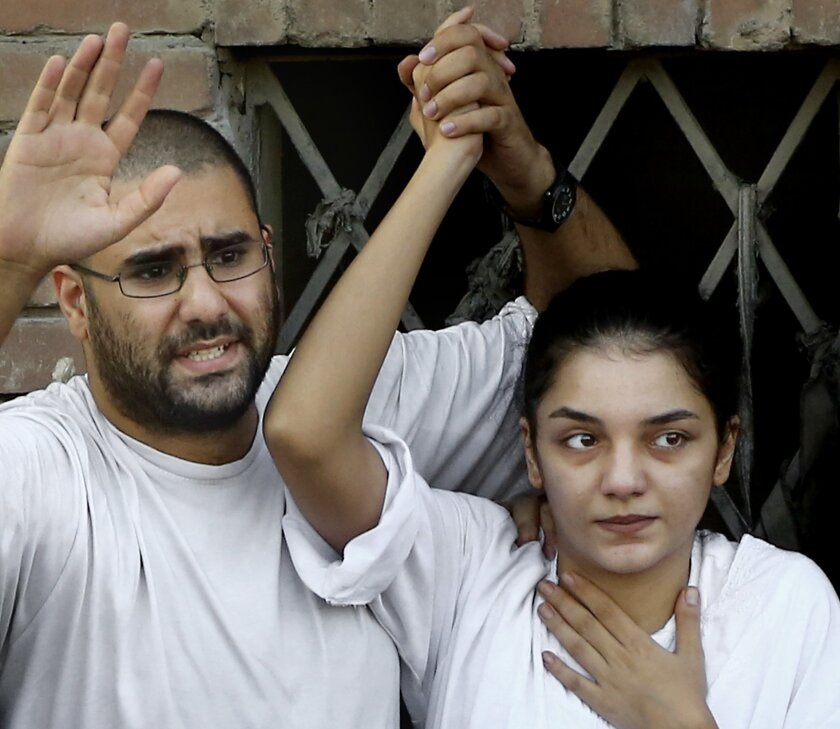 FILE - In this Thursday, Aug. 28, 2014 file photo, Surrounded by plainclothes policemen, Egyptian prominent blogger Alaa Abdel-Fattah, left, speaks to the crowd after attending, with his sister Sanaa, right, their father Ahmed Seif funeral in Cairo, Egypt. When 22-year-old Sanaa was summoned for qu