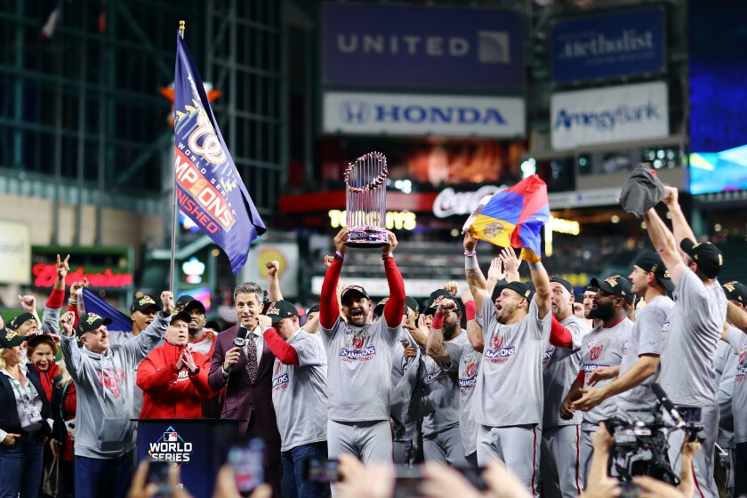 Washington Nationals Manager Dave Martinez hoists the Commissioners Trophy after winning the World Series.