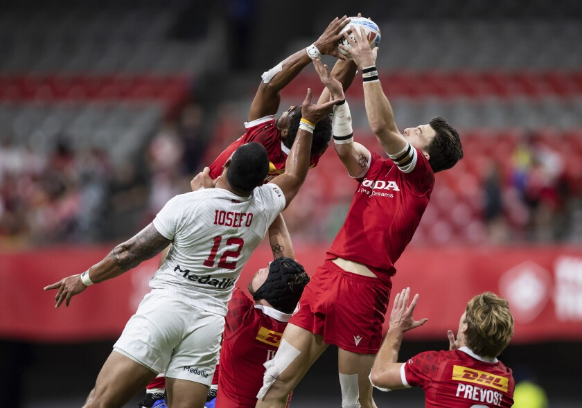 United States' Martin Iosefo (12) vies for the ball against Canada's Andrew Coe, right, and Josiah Morra, back, during an HSBC Canada Sevens rugby game in Vancouver, British Columbia, Saturday, Sept. 18, 2021. (Darryl Dyck/The Canadian Press via AP)