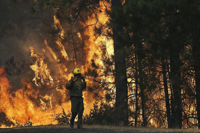 "FILE - This Aug. 25, 2013 file photo shows firefighter A.J. Tevis watching the flames of the Rim Fire near Yosemite National Park, Calif. The House has approved a wide-ranging bill that speeds logging of trees burned in last year's massive Rim Fire in California. The measure also allows vehicular access to North Carolina's Cape Hatteras National Seashore, extends livestock grazing permits on federal land in the West and lifts longstanding restrictions on canoes, rafts and other ""hand-propelled"" watercraft in Yellowstone and Grand Teton national parks. (AP Photo/Jae C. Hong, File)"