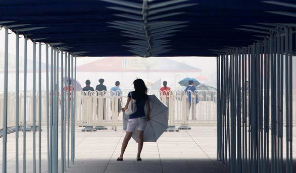 A Chinese girl with a parasol waits outside the National Stadium at the Beijing 2008 Olympics in hazy and humid weather.