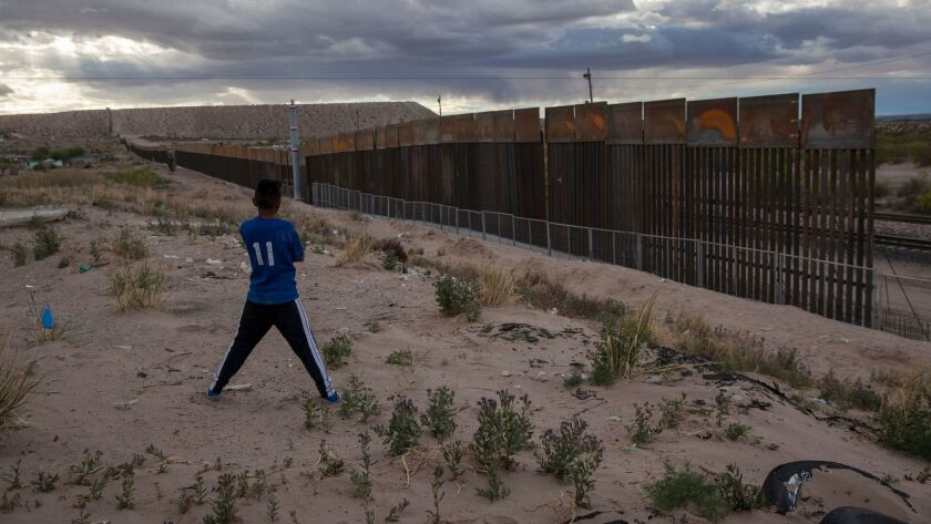 FILE - In this March 29, 2017, file photo, a youth looks at a new, taller fence being built along U.