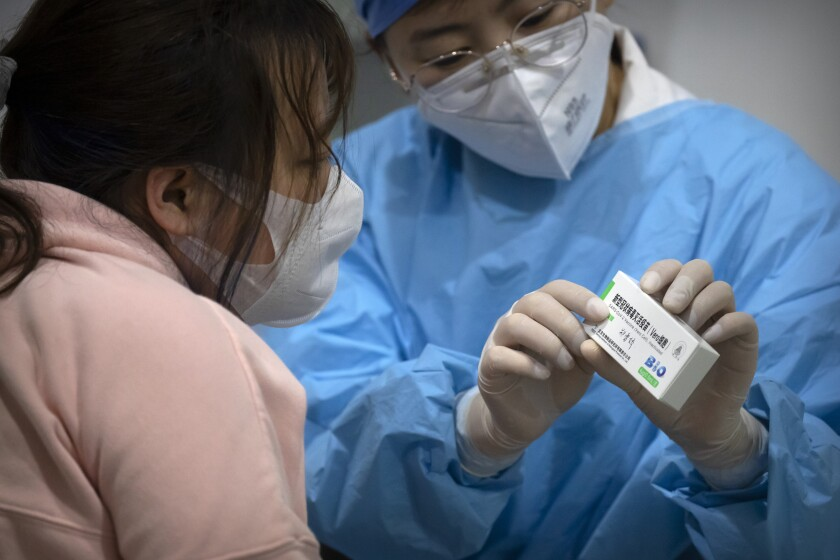 A medical worker holds a package of Sinopharm vaccine in Beijing.