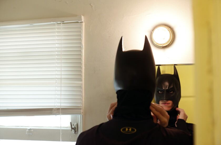 Aspiring actor Austin Franklin gets dressed up as Batman at his home in Hollywood before heading out to perform on Hollywood Boulevard on April 15, 2016.