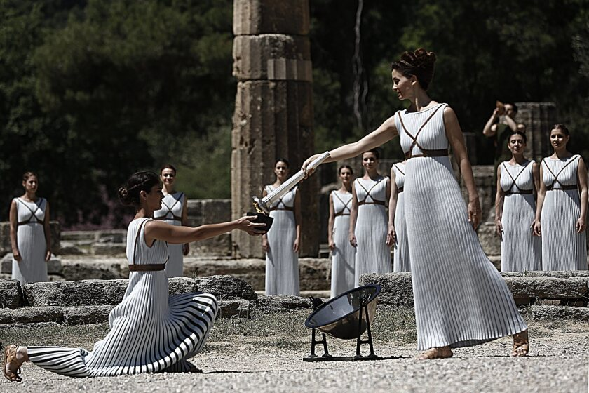 Greek actress Katerina Lechou, right, playing the role of high priestess, lights the Olympic flame Thursday at the site of ancient Olympia in Greece.