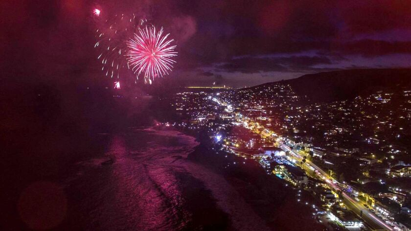 Laguna beaNorth coast highway stretches along as a bright red firework bursts over the ocean and cit