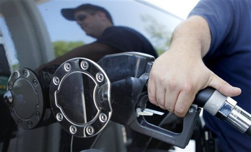 Kevin Stearns of Oxford, Mass., fills up his pick up truck at a gas station in Milford, Mass., Wednesday, May 26, 2010. Gasoline prices dropped Thursday for the second week in a row, and they'll be pushed even lower as oil prices continue to tumble.(AP Photo/Charles Krupa)