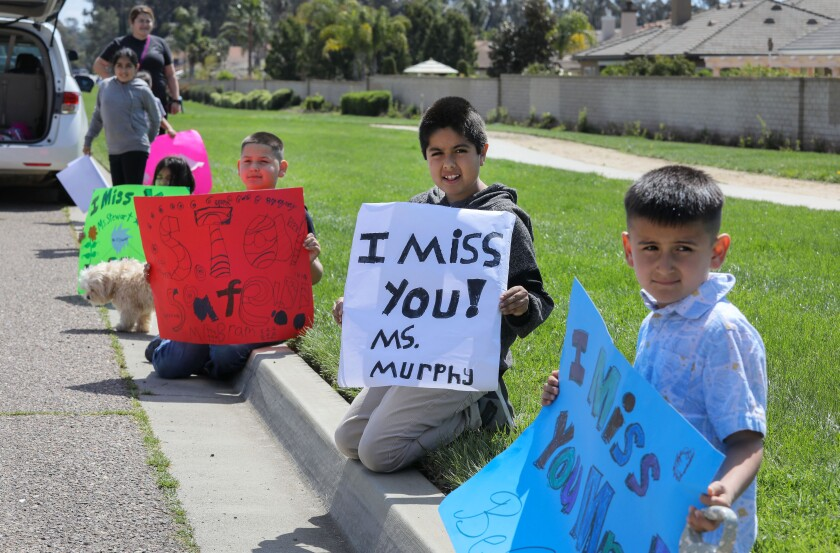 Reidy Creek Elementary School students wait for a caravan of their teachers to drive by and greet them in Escondido.