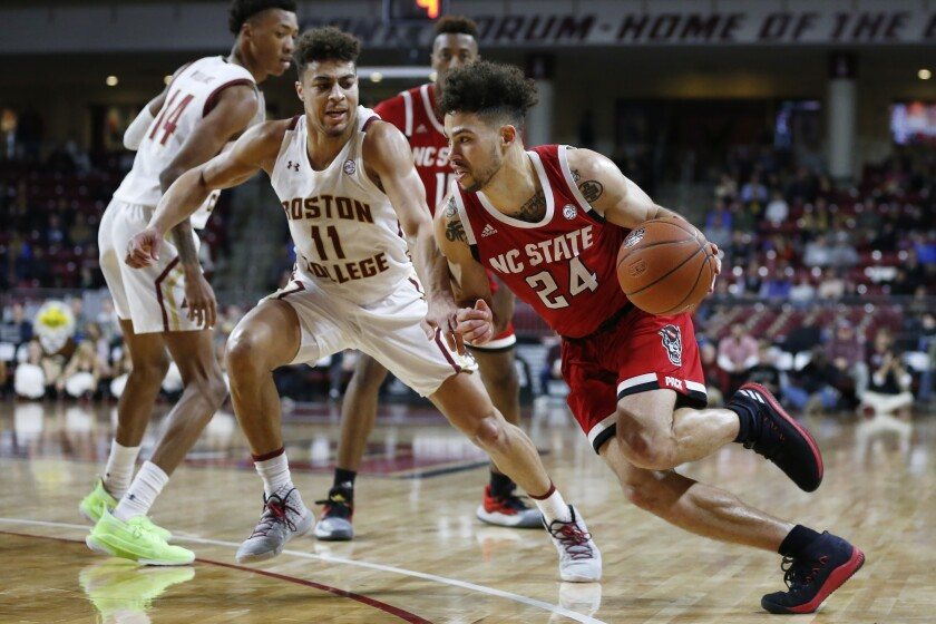 FILE - In this Feb. 16, 2020, file photo, North Carolina State's Devon Daniels (24) drives past Boston College's Derryck Thornton (11) during the second half of an NCAA college basketball game in Boston. Daniels returns to the Wolfpack after averaging 12.7 points last season. (AP Photo/Michael Dwyer, File)