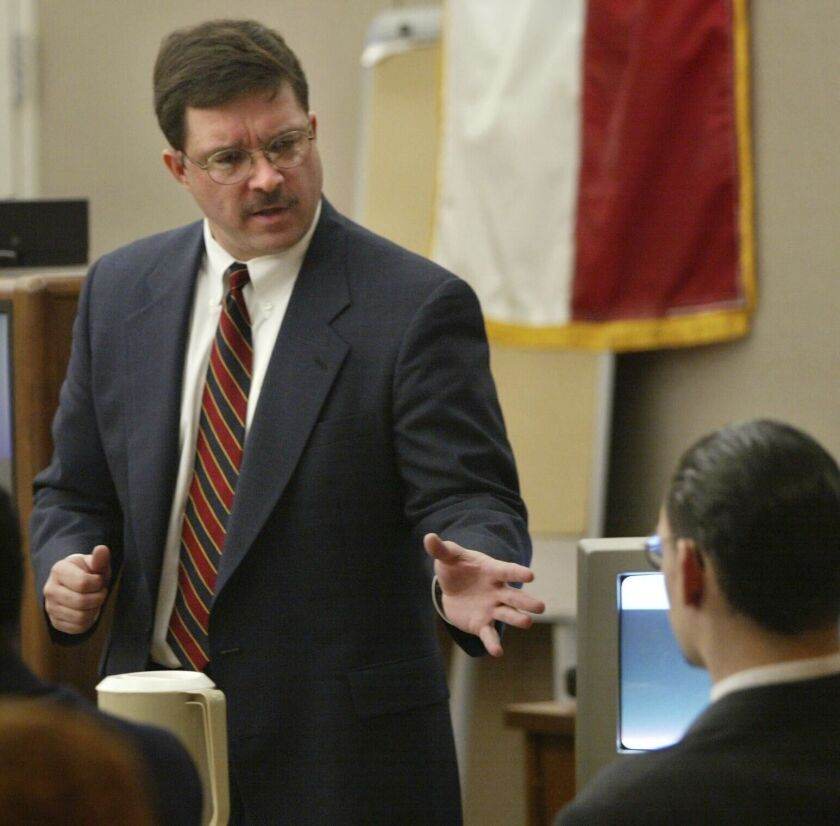 Prosecution attorney Rick Jackson, left, makes his closing arguments in front of Donald Newbury during Newbury's capital murder trial on Friday, Jan. 18, 2002 in Dallas. The former Dallas County prosecutor has surrendered his law license after the State Bar of Texas said he withheld evidence that led to the wrongful convictions of two men who spent 14 years in prison in the fatal stabbing of a pastor. (Andy Scott/The Dallas Morning News via AP, file)