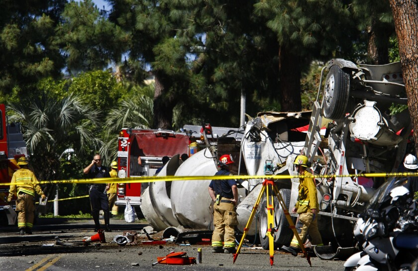 Firefighters and police officers work at the scene where a cement truck overturned May 9 on the 1000 block of Loma Vista Drive in Beverly Hills.