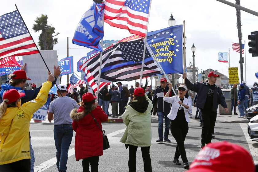 Pro-Trump protesters rally Saturday afternoon at Pier Plaza in downtown Huntington Beach.