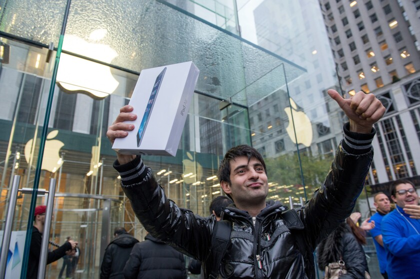 Apple posted stronger results than expected this week. Above, a customer celebrates his purchase of the new iPad Air in New York in November.