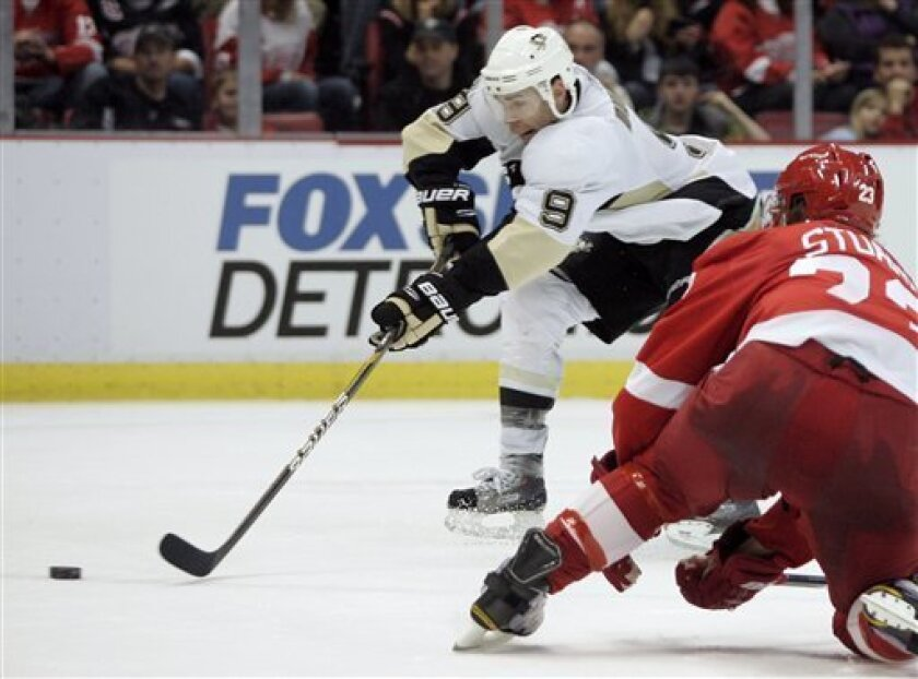 Pittsburgh Penguins' Pascal Dupuis (9) goes past Detroit Red Wings' Brad Stuart, right, and takes a shot on goal duirng the second period of an NHL hockey game Monday, March 21, 2011, in Detroit. The shot missed, but Dupuis scored on the rebound. (AP Photo/Duane Burleson)