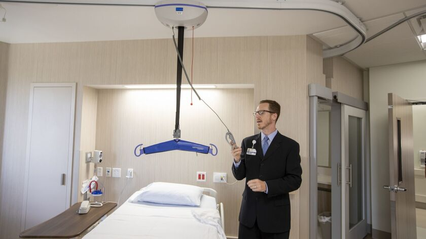 Mark Giavinic, the director of rehabilitation services, demonstrates a lift for patients who have a