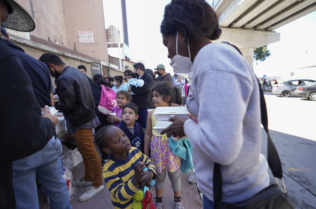 Migrants, including small children, wait in line for food.