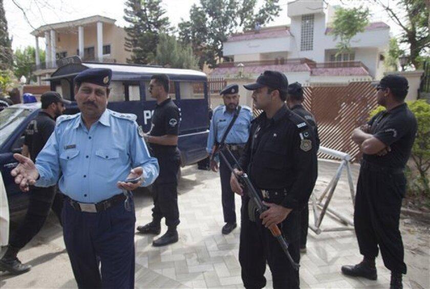 Pakistani police officers secure the area outside the house where Osama bin Laden's family are being detained in Islamabad, Pakistan, on Monday, April 2, 2012 in Islamabad, Pakistan. The lawyer for Osama bin Laden's family says a Pakistani court has convicted his three widows and two of his daughters on charges of illegally living in Pakistan and sentenced them to 45-days in prison. (AP Photo/B.K. Bangash)