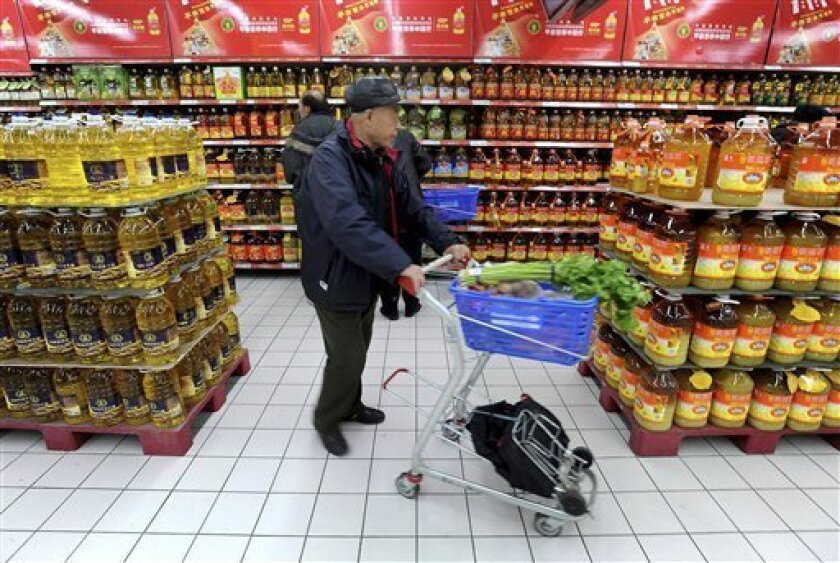 In this photo taken Tuesday Dec. 8, 2009, a customer pushes his cart in a supermarket in Shenyang, in northeast China's Liaoning province. The slump in China's exports eased in November as global demand improved while strong gains in industrial output and retail sales showed that the recovery in the world's third-biggest economy is gathering momentum. (AP Photo)