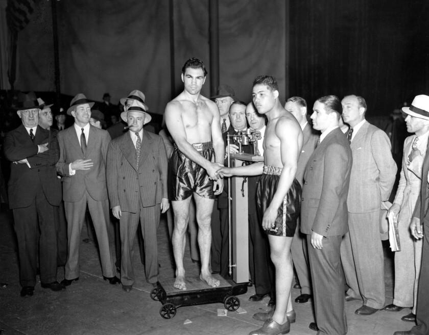 Max Schmeling, on scale, and Joe Louis shake hands at the weigh-in ceremony for their bout at Yankee Stadium on June 18, 1936.