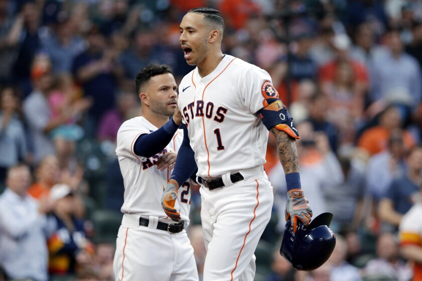 Houston Astros' Jose Altuve, left, pats Carlos Correa (1) as they celebrate Correa's home run during the second inning of a baseball game against the Oakland Athletics on Thursday, April 8, 2021, in Houston. (AP Photo/Michael Wyke)