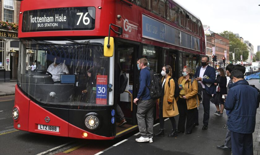 People board a bus outside Waterloo station in London, Wednesday, Sept. 23, 2020, after Prime Minister Boris Johnson announced a range of new restrictions to combat the rise in coronavirus cases in England, Wednesday, Sept. 23, 2020. (Dominic Lipinski/PA via AP)