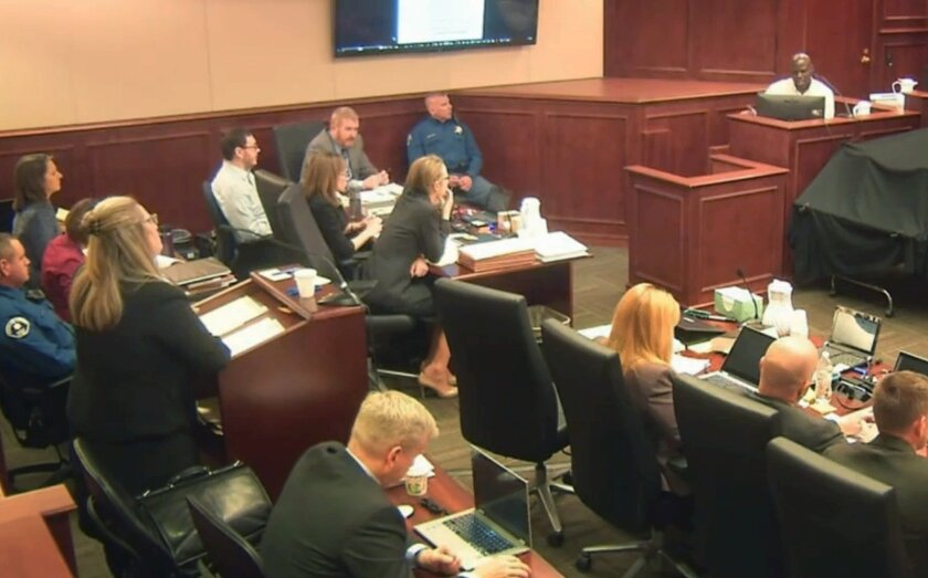 In this image taken from Colorado Judicial Department video, Aurora theater shooter James Holmes, left rear in light-colored shirt, listens during witness testimony last month at his trial in Centennial, Colo.