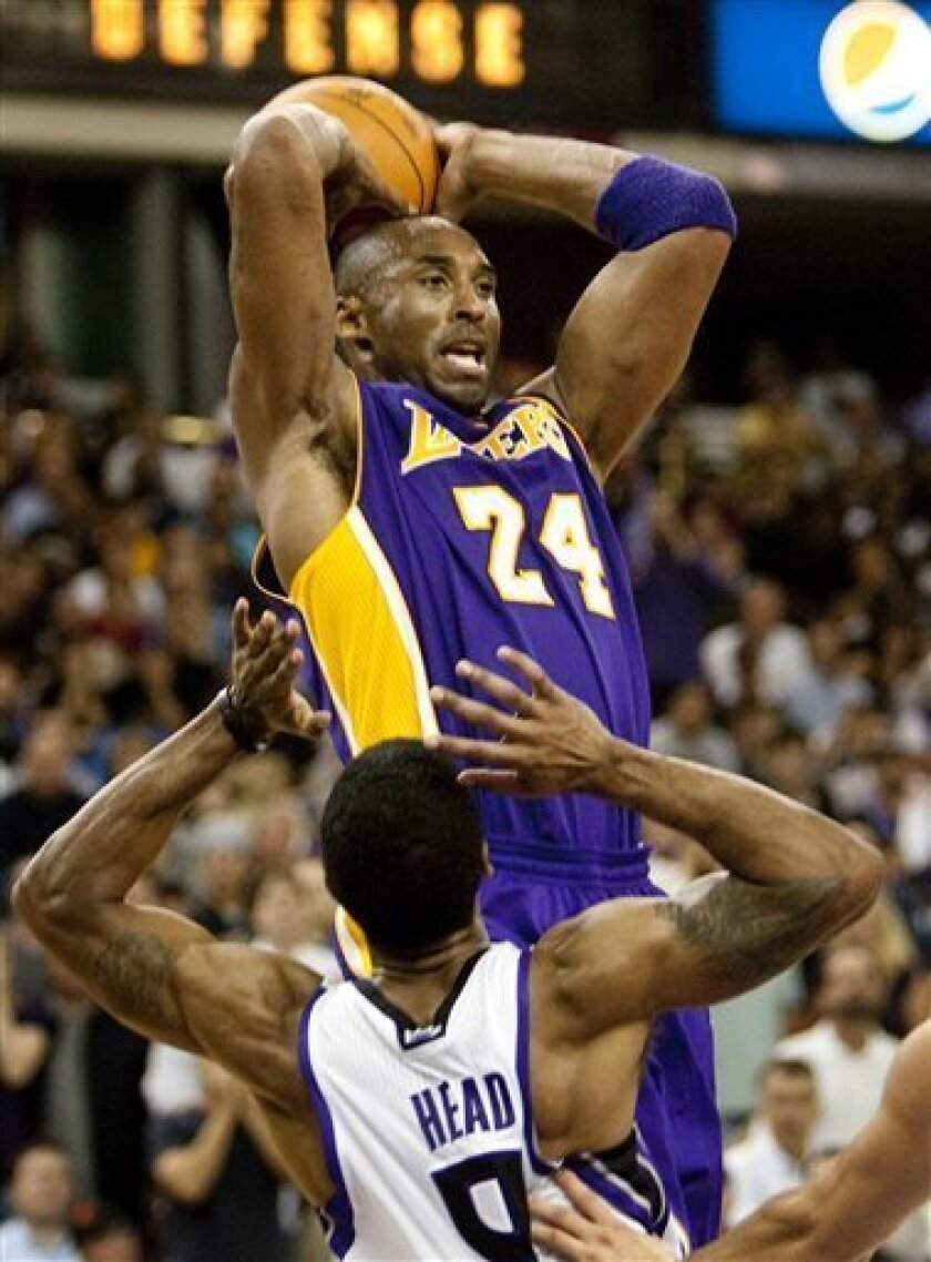 Los Angeles Lakers' Kobe Bryant looks for someone to pass to as he is guarded by the Sacramento Kings' Luther Head (9) in the second half in Sacramento, Calif, Wednesday Nov. 3, 2010. Bryant scored 30 points as the Lakers beat the Kings 112 to 100. (AP Photo/Robert Durell)