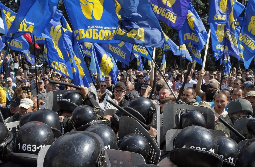Demonstrators waving flags of the nationalist Svoboda party clash with police during an Aug. 31 protest in front of the Ukrainian parliament in Kiev, opposing a bill granting autonomy to Ukraine's restive eastern regions.