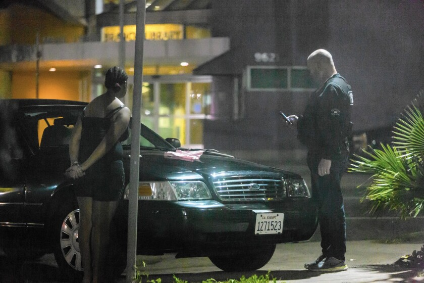 A police officer questions a girl in January in a South Los Angeles area known for sex trafficking involving minors.