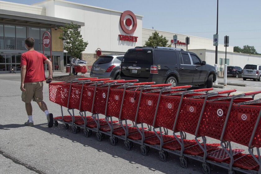 A Target employee returns shopping carts from the parking lot, in Omaha, Neb., Tuesday, June 16, 2020. American shoppers ramped up their spending on store purchases by a record 17.7% from April to May, delivering a dose of energy for retailers that have been reeling since the coronavirus shut down businesses, flattened the economy and paralyzed consumers during the previous two months. (AP Photo/Nati Harnik)
