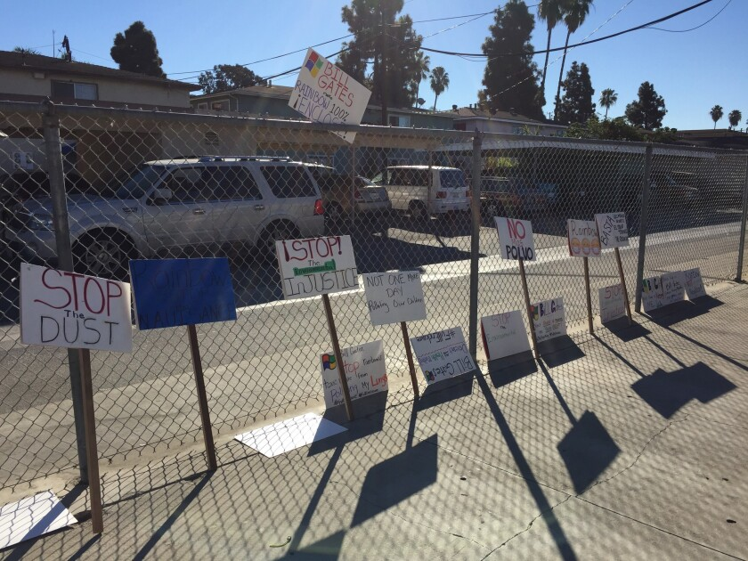 Signs expressing neighbors' complaints about dust, odors and other problems associated with Rainbow Environmental Services' waste and recycling facility in Huntington Beach are posted outside a South Coast Air Quality Management District hearing Saturday in Huntington Beach.