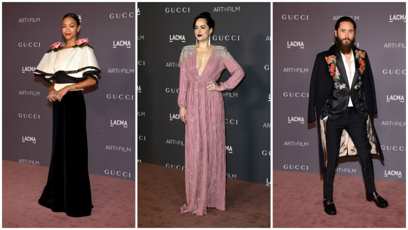 From left, attendees Zoe Saldana (in a black velvet gown with oversize plissé sculpted shoulders and hand-made silk decorative 3-D flowers on the collar from Gucci's fall/winter 2017 collection); Dakota Johnson (in a pink silk satin gown with a deep V-neck and crystal embroidered appliqués on the shoulders from Gucci's spring/summer 2018 collection); and Jared Leto (in a black jacquard evening jacket with floral embroidery detail from the Gucci 2018 Cruise collection worn under a black velvet floral embroidered coat).